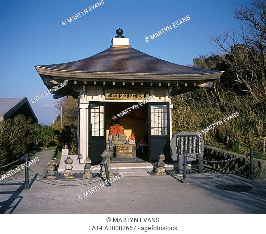 Small Shinto shrine. Bedecked effigy. Stone tablet with Japanese writing