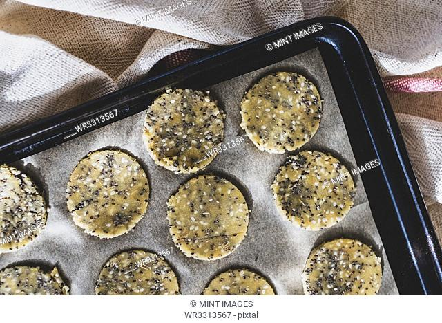 High angle close up of seeded cracker dough on a baking tray