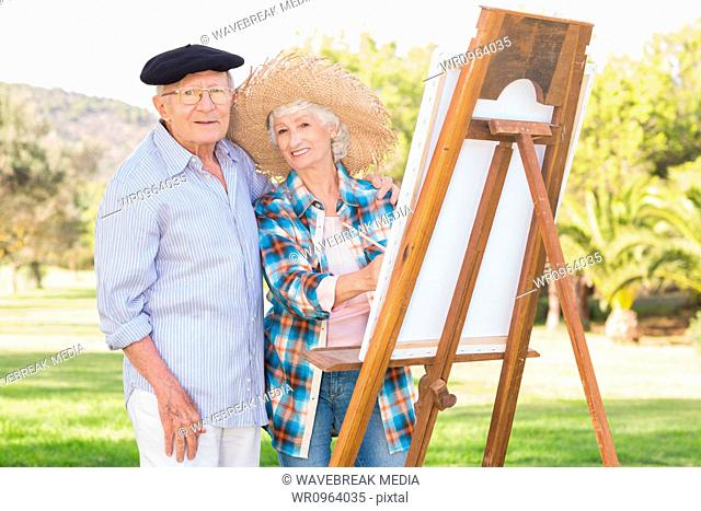 Portrait of older couple painting in the park