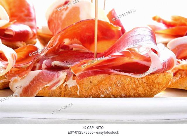 spanish pinchos de jamon, serrano ham served on bread