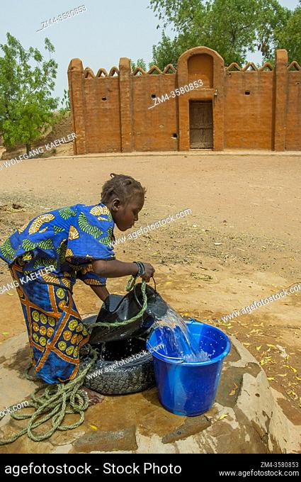 A teenage girl is getting water from a well (the palace of the Bambara Kingdom in the background) in the Segoukoro village (Bambara tribe) near Segou city in...