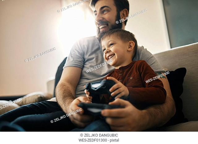 Happy father and little son sitting together on the couch playing computer game