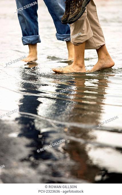 Malaysia, Man And Woman In Bare Feet Holding Shoes And Walking In Shallow Water; Malacca