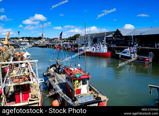 Fishing boats tied up in the harbour at Whitstable, Kent, England