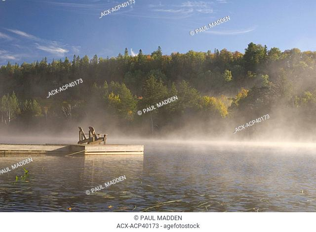 Autumn view of Dock with Muskoka chairs, Oxtongue Lake, Ontario, Canada