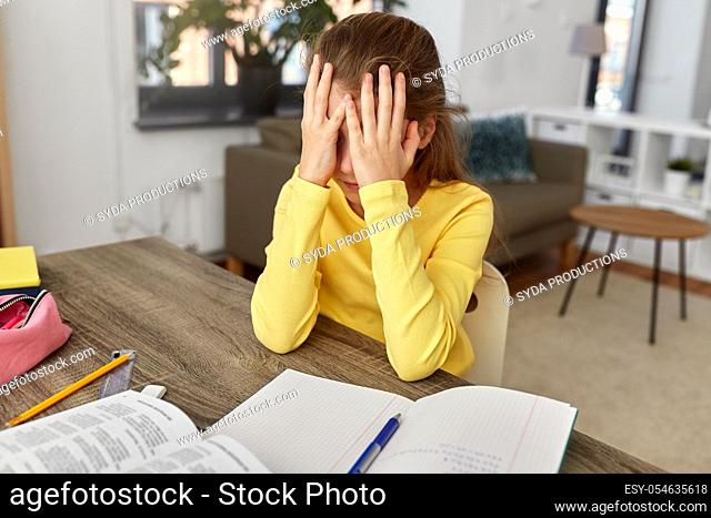 stressed little student girl learning at home