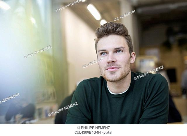 Mid adult man sitting gazing in cafe