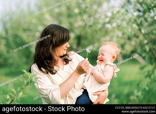 A mother and her daughter playing together with a dandelion