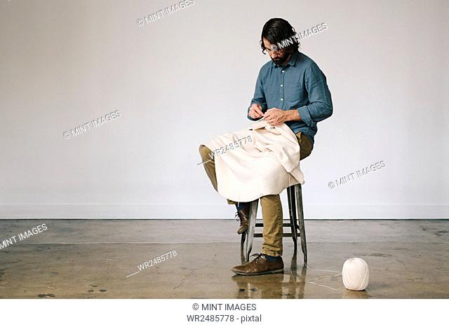 A male artist working, using string to crochet and create an art piece
