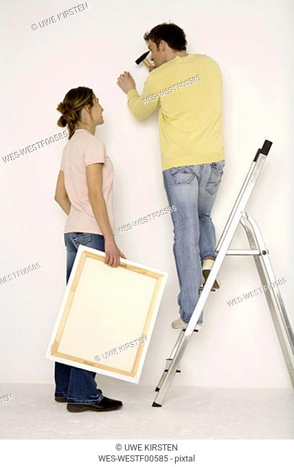 Young couple hanging up painting, man standing on ladder