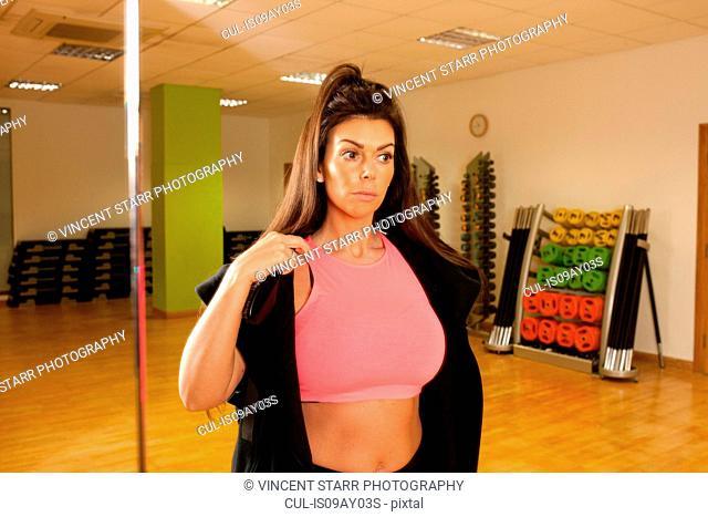 Women in gym wearing crop top looking away