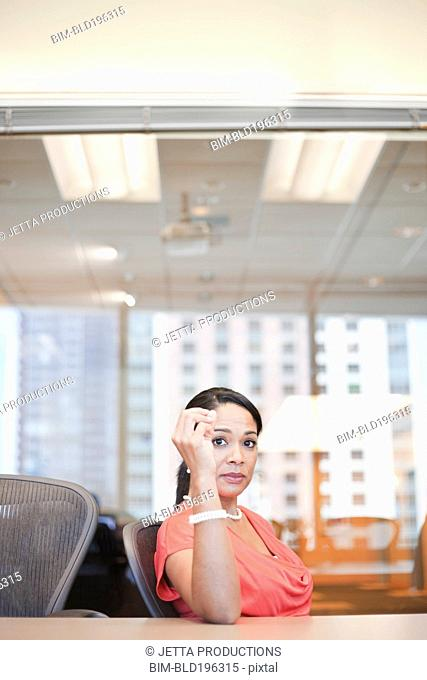 Serious Black businesswoman sitting in conference room