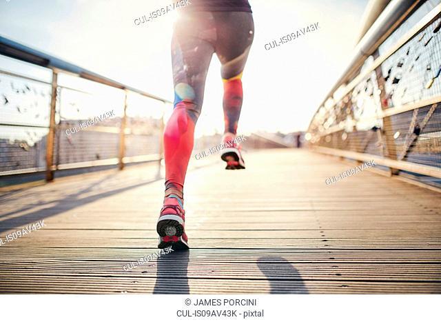 Rear waist down view of female runner running across footbridge
