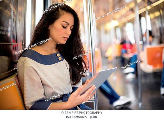 Mid adult women using digital tablet on subway, New York