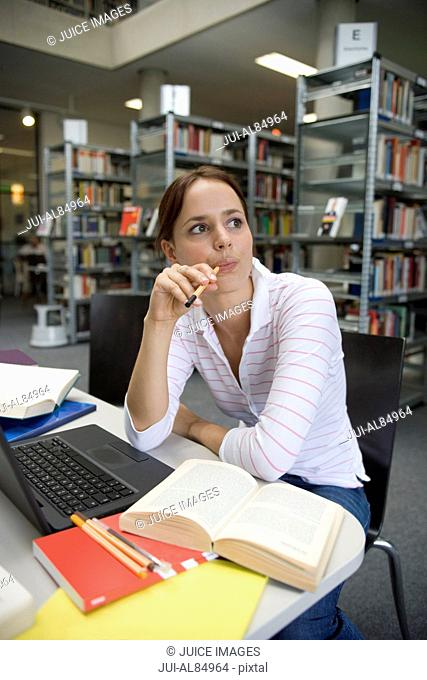 Female teenage student studying with laptop in library