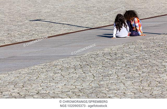 Child is bored on the road asphalt