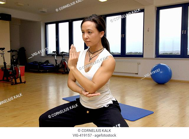 GERMANY, GEESTHACHT, 06.04.2007, Woman is making some Yoga exercises within a gym. - Geesthacht, Schleswig-Holstein, Germany, 06/04/2007