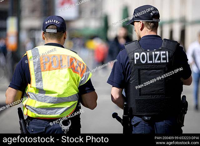 09 April 2020, Berlin: Two police officers of the Berlin Police's Focal Point and Presence Unit (BPE) are patrolling Alexanderplatz