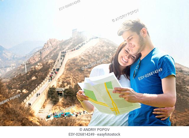Young Couple Looking At Map In Front Of Great Wall Of China