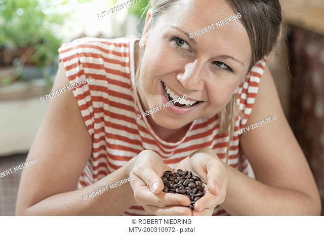 Young woman with handful of roasted coffee beans