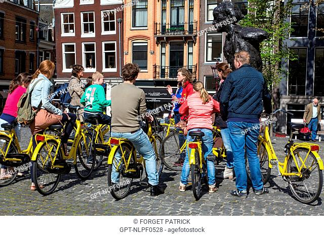 GROUP OF TOURISTS ON BIKES WITH A TOUR GUIDE IN FRONT OF THE STATUE OF MULTATULI ON THE TORENSLUIS BRIDGE, SINGEL, AMSTERDAM, HOLLAND