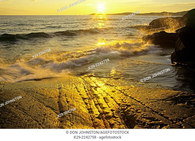 Sunset on Lake Superior and shoreline rocks with glacial scratches, Pukaskwa National Park, Ontario, Canada