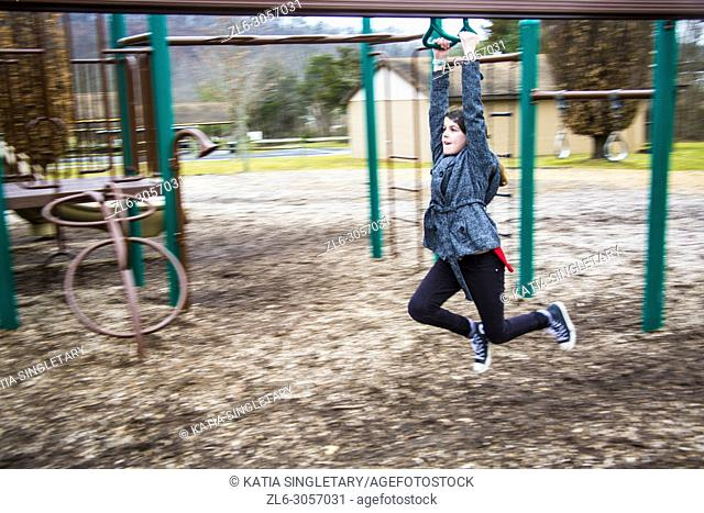 Caucasian handsome preteen/ teen wearing black leggings and white and black jacket, she is playing in kids playground and going down the Zipline