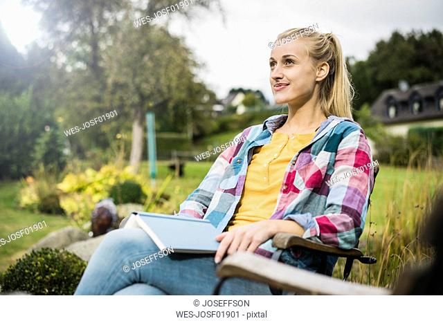 Smiling young woman with book relaxing in garden
