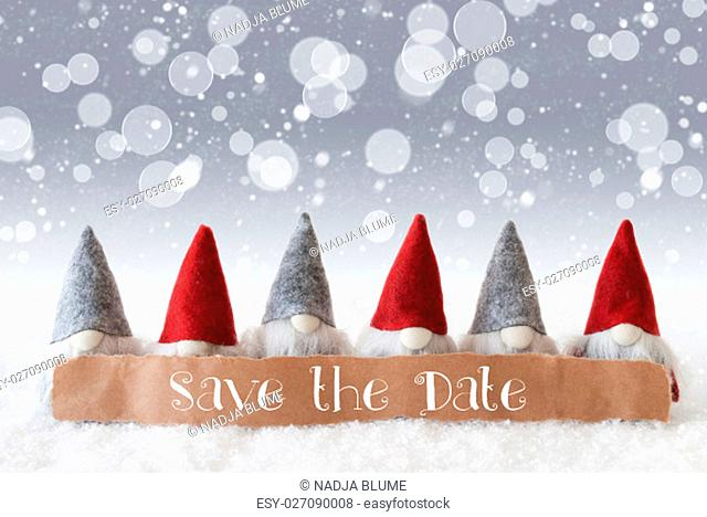 Label With English Text Save The Date. Christmas Greeting Card With Gnomes. Sparkling Bokeh And Silver Background With Snow And Snowflakes