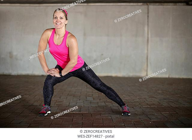 Smiling sportive woman stretching