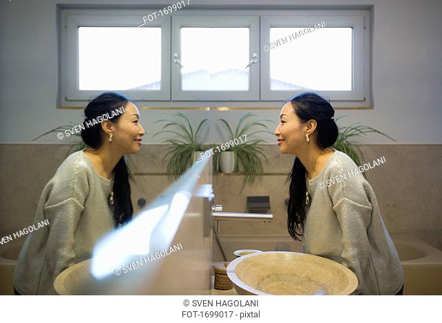 Side view of smiling mature woman looking at mirror reflection in bathroom
