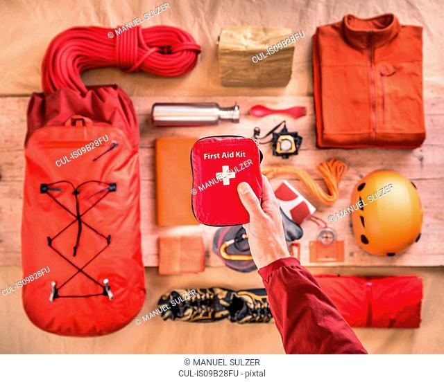 Overhead view of man's hand holding first aid kit above climbing equipment packing with climbing helmet, rucksack and climbing ropes