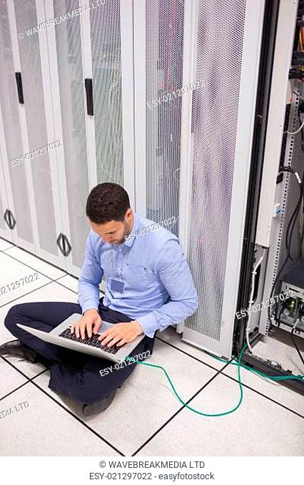 Technician connecting laptop to servers in data center