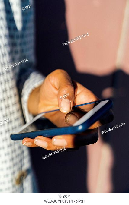 Hands of woman using smartphone, close up