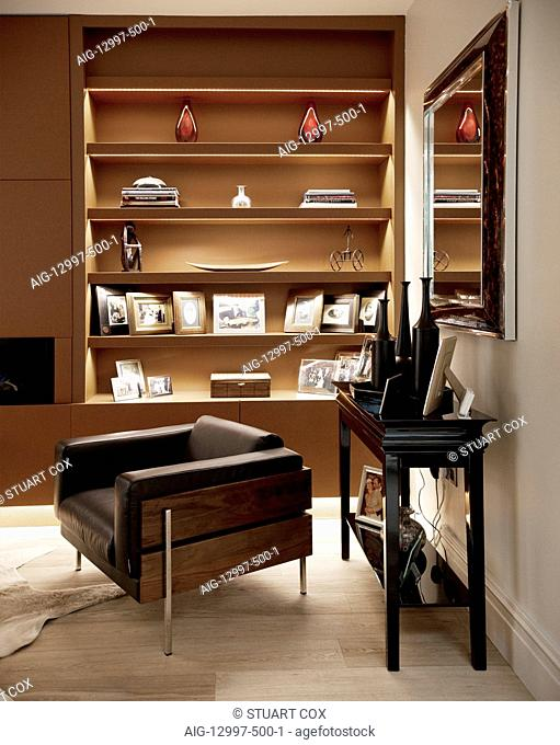 Lit bookshelf and mirror with brown leather Forum armchair by Robin Day, Addison Road, UK