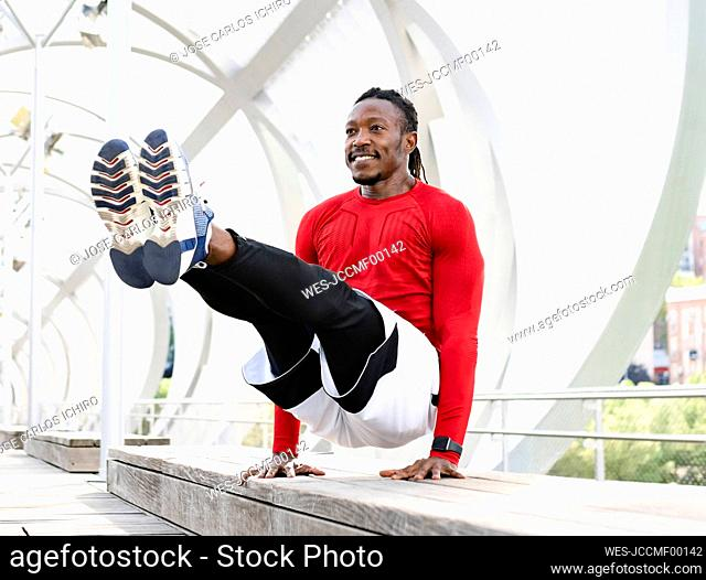Smiling athlete doing handstand on bench at walkway