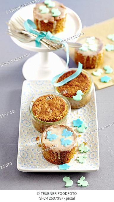 Mini carrot cakes baked in jars decorated with icing and fondant animals