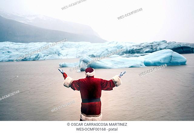 Iceland, rear view of a man disguised as Santa Claus standing at a glacier raising his arms