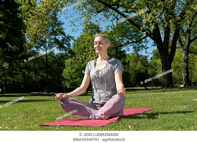 Woman in training clothing sitting cross-legged on pink mat in the park