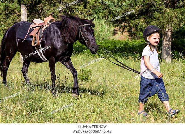 Greece, Corfu, Agios Georgios, little girl leading horse on a meadow