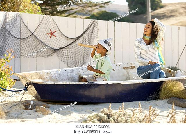 Mixed race mother and son pretending to sail in a boat