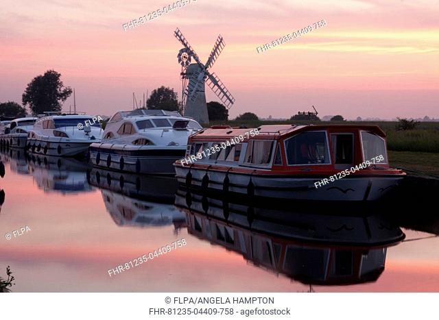 Pleasure boats moored near windpump at sunset, Thurne Windpump (Morse's Mill), Thurne Dyke, River Thurne, The Broads N.P., Norfolk, England, July