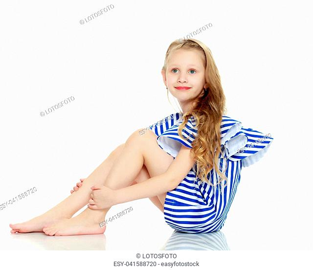 Adorable little blond girl in very short summer striped dress.She sits on the floor barefoot, turning sideways to the camera