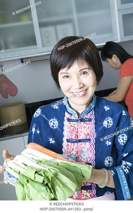 Portrait of a senior woman holding vegetables and smiling in a domestic kitchen