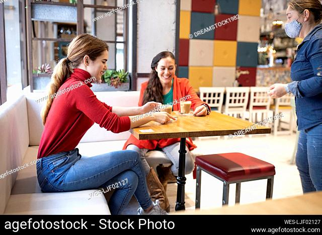 Waitress looking at smiling female friends having coffee in cafe during COVID-19