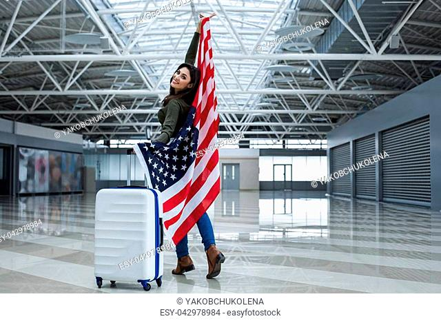 Satisfied female left the plane. She is standing at the hall with bag and banner. Copy space in right side