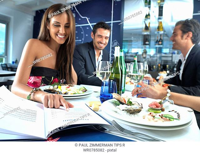 Woman with friends at restaurant looking at menu