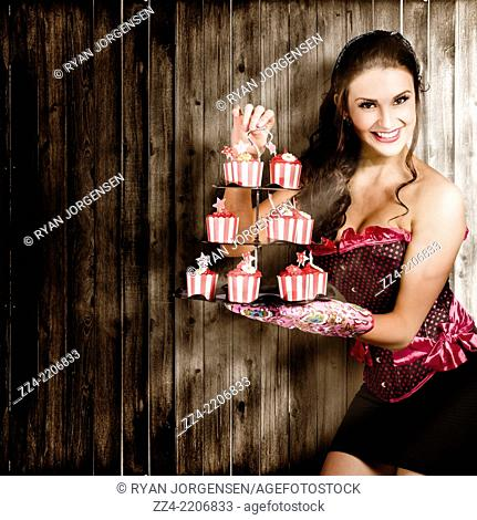Beautiful young smiling retro pinup woman serving up a tiered food platter of sweet cake inside rustic wooden house. Boutique cakes conceptual