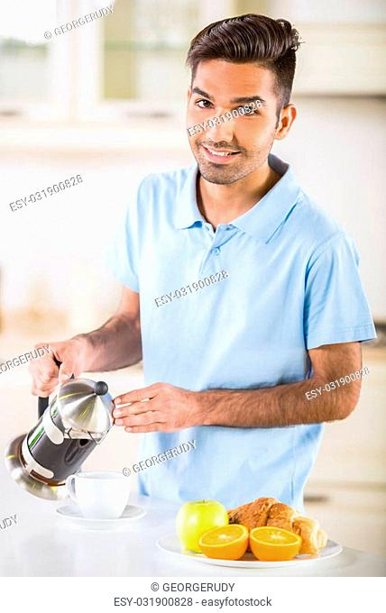 Young handsome man in blue t-shirt drinking coffee and eating fruits for breakfast