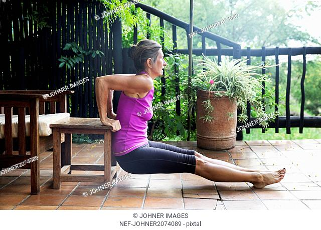 Mature woman exercising on balcony